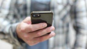 O homem novo à moda em uma camisa de manta usa um smartphone video estoque