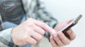 O homem novo à moda em uma camisa de manta usa um smartphone vídeos de arquivo