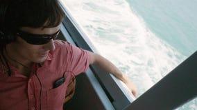 O homem novo à moda feliz sunglasseslisten dentro à música perto do mar pelo mar ao flutuar Movimento lento 1920x1080 vídeos de arquivo