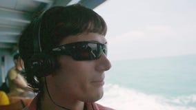 O homem novo à moda feliz sunglasseslisten dentro à música perto do mar pelo mar ao flutuar Movimento lento 1920x1080 filme