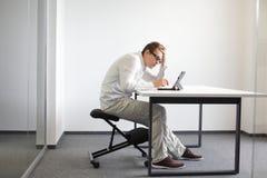 O homem novo é dobrado sobre sua tabuleta. Postura de assento má no trabalho Fotos de Stock