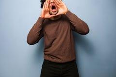 O homem novo é gritaria para receber transversalmente sua mensagem fotografia de stock royalty free