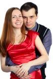 O homem novo abraça a mulher bonita no vermelho. Fotografia de Stock