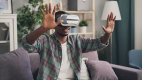 O homem novo afro-americano está jogando o jogo nos vidros aumentados da realidade que têm o divertimento apenas em casa que vest