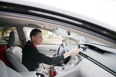 O homem novo ajusta-se - acima do telefone celular no carro futurista Imagens de Stock