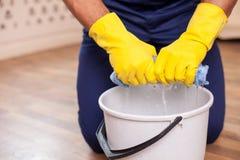 O homem novo alegre está fazendo a limpeza em sua casa Imagens de Stock