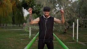 O homem novo amassa antes do exercício nas barras desiguais video estoque