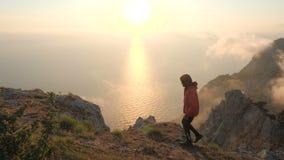 O homem novo anda ao longo da borda de um penhasco observando o por do sol colorido dramático bonito acima de um mar de uma monta filme