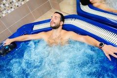O homem novo aprecia e relaxa no centro dos termas imagem de stock royalty free
