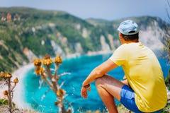 O homem novo aprecia a praia de Petani em Kefalonia Panorama pitoresco altamente entusiasmado da baía azul esmeralda da lagoa de imagem de stock