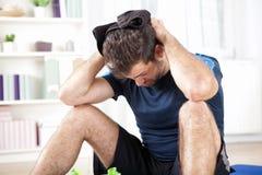 O homem novo apto que limpa o seu suou após o exercício foto de stock