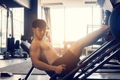 O homem novo asiático desportivo dá certo o trabalho pesado na máquina da imprensa do pé imagens de stock