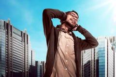 O homem novo asiático escuta a música através do fones de ouvido Fotografia de Stock Royalty Free