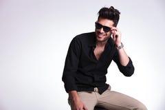 O homem novo assentado guardara seus óculos de sol e sorrisos Imagens de Stock Royalty Free