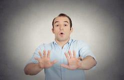 O homem novo assustado que levanta a mão diz até não a parada Imagem de Stock