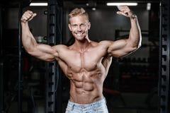 O homem novo atlético forte e considerável muscles o Abs e a aptidão e o halterofilismo do bíceps fotos de stock royalty free