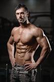 O homem novo atlético forte e considerável muscles o Abs e o bíceps Fotografia de Stock