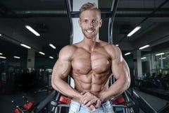 O homem novo atlético forte e considerável muscles o Abs e o bíceps imagens de stock royalty free