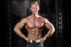 O homem novo atlético forte e considerável muscles o Abs e o bíceps fotos de stock royalty free