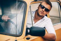 O homem novo atrás da roda de um carro retro da aparência bonita Fotografia de Stock