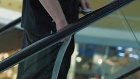 O homem novo aumenta na escada rolante, põe algo em seu bolso video estoque
