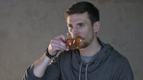 O homem novo bebe o chá de um vidro filme