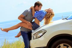 O homem novo beija a mulher que senta-se pelo carro contra o mar Fotos de Stock Royalty Free