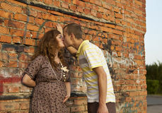 O homem novo beija sua esposa grávida Fotografia de Stock