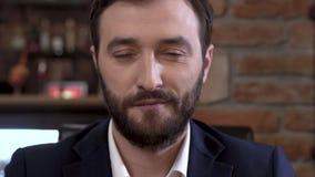 O homem novo bem vestido, seguro com uma barba é lookig seguramente na câmera closeup vídeos de arquivo