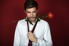 O homem novo bonito guarda uma rosa com dentes Fotografia de Stock Royalty Free