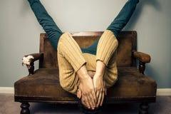 O homem novo cansado é de cabeça para baixo no sofá velho Fotos de Stock Royalty Free
