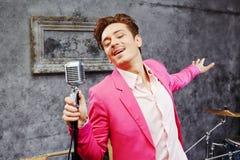 O homem novo canta no microfone com seus olhos fechados Imagem de Stock