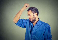 O homem novo, cheirar, aspirando sua axila, algo tresanda, odor muito mau, hediondo Imagem de Stock