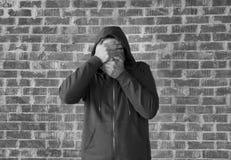 O homem novo cobre seus olhos e boca com as mãos, preto e branco Fotos de Stock