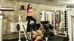 O homem novo com amiga está treinando no gym vídeos de arquivo