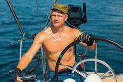 O homem novo com corpo despido dirige o barco de navigação imagem de stock royalty free