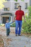 O homem novo com filho pequeno vai no asfalto Fotografia de Stock Royalty Free