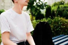 O homem novo com fones de ouvido senta-se no parque Vista próxima Imagens de Stock