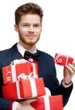 O homem novo com laço leva muitos presentes Fotos de Stock Royalty Free