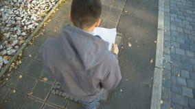 O homem novo com mapa da cidade perdeu na rua, turista que procura pelo lugar do destino vídeos de arquivo