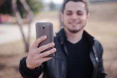 O homem novo com telefone celular que anda, fundo é cidade blured Fotografia de Stock