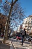 O homem novo com trouxa monta um 'trotinette' elétrico do impulso na estrada, Barcelona, Espanha imagem de stock