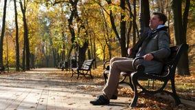 O homem novo com trouxa senta-se em um banco no parque do outono vídeos de arquivo