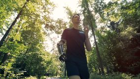 O homem novo com um braço protético biônico futurista está movimentando-se ao longo da floresta