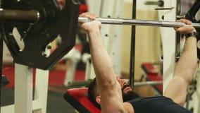 o homem novo com uma barba na camisa preta de T está treinando no gym filme