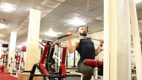 o homem novo com uma barba na camisa preta de T está treinando no gym vídeos de arquivo