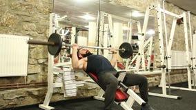 o homem novo com uma barba na camisa preta de T está treinando no gym video estoque