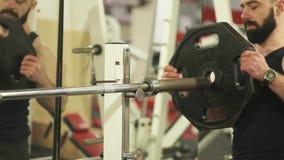 O homem novo com uma barba no t-shirt preto está treinando no gym video estoque