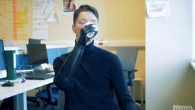 O homem novo com uma mão futurista biônico artificial está bebendo de um copo Homem do conceito futuro
