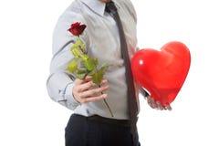 O homem novo com uma rosa vermelha e o coração balloon Imagem de Stock